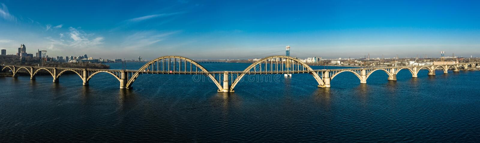 Aerial panoramic view on old arch railway Merefo-Kherson bridge across the Dnieper river in Dnepropetrovsk, Ukraine.  royalty free stock image