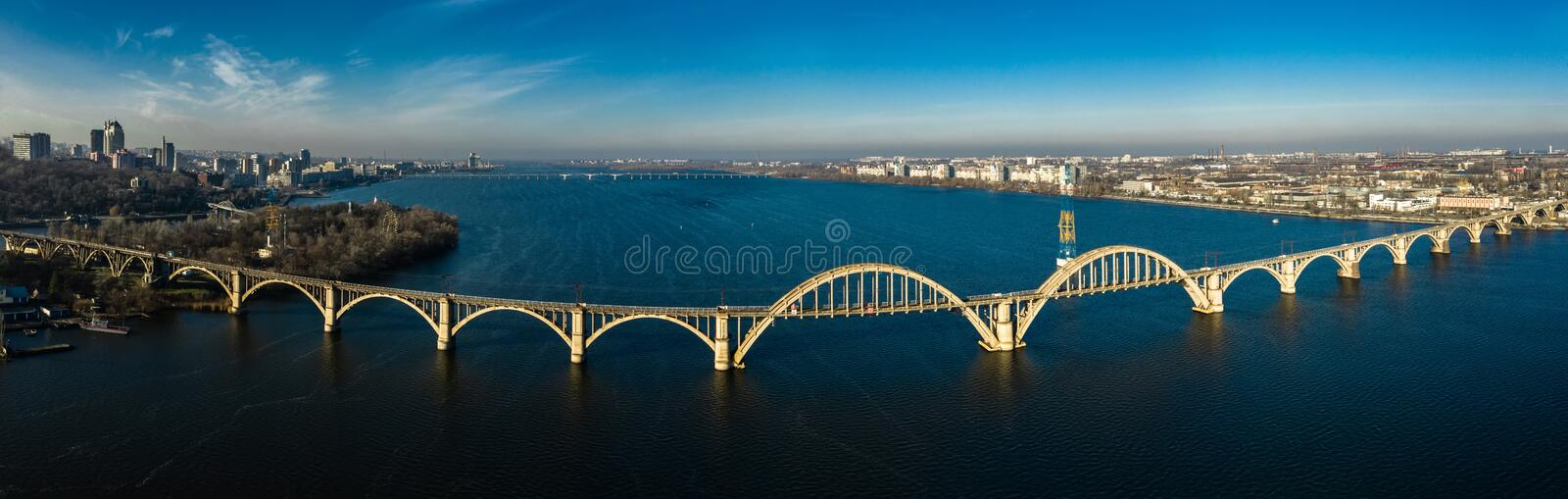 Aerial panoramic view on old arch railway Merefo-Kherson bridge across the Dnieper river in Dnepropetrovsk, Ukraine.  royalty free stock photography