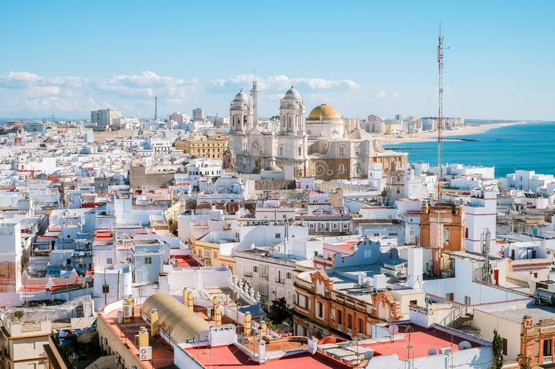 Aerial panoramic view of the old city rooftops and Cathedral de Santa Cruz in the afternoon. From tower Tavira in Cadiz, Andalusia, Spain royalty free stock photo