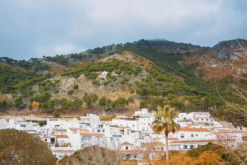 Aerial panoramic view over the roofs of a small touristic white-washed village at Malaga province (Andalusia, Spain) and mountain stock images