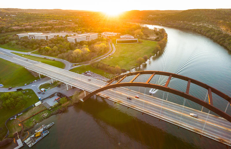 Aerial Pennybacker Bridge or 360 Bridge Austin Texas Landscape Over Colorado River Town Lake. At Sunset. The Bright sun casts a large solar flare as it sets stock photo