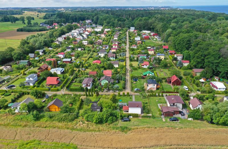 Aerial perspective drone view on allotment gardens with high density of houses in forest, sea and agricultural fields surroundings royalty free stock photos