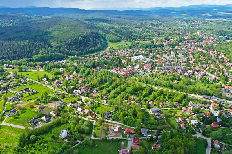 Aerial perspective view on sudety mountains with touristic city in the valley surrounded by meadows, forest and rapeseed fields. Polanica zdroj landscape stock photo