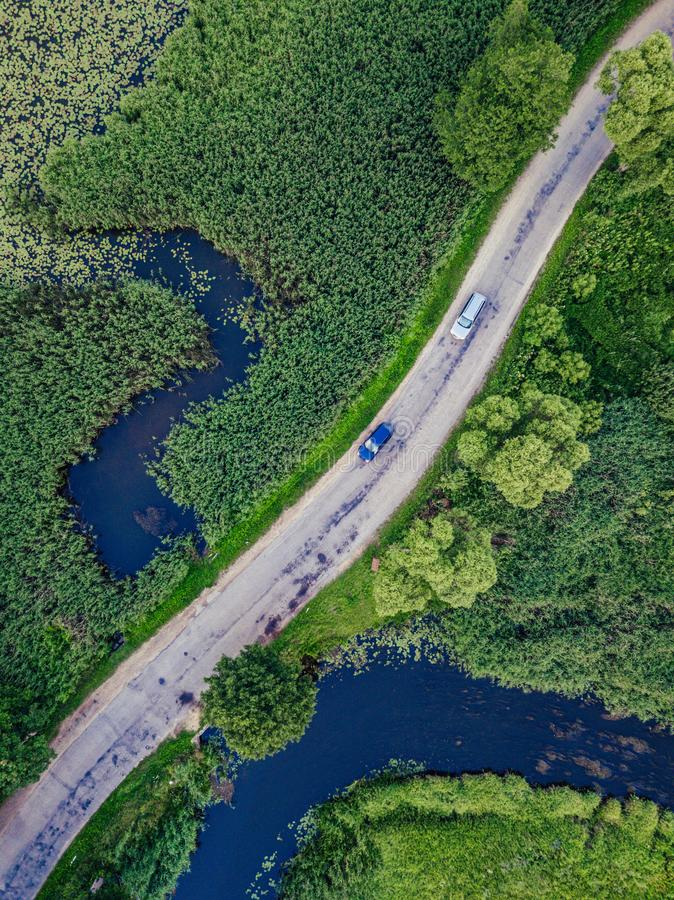 Aerial Photo of Car Driving on the Road going by the River under the Trees, Top Down View in Early Spring on Sunny Day royalty free stock images