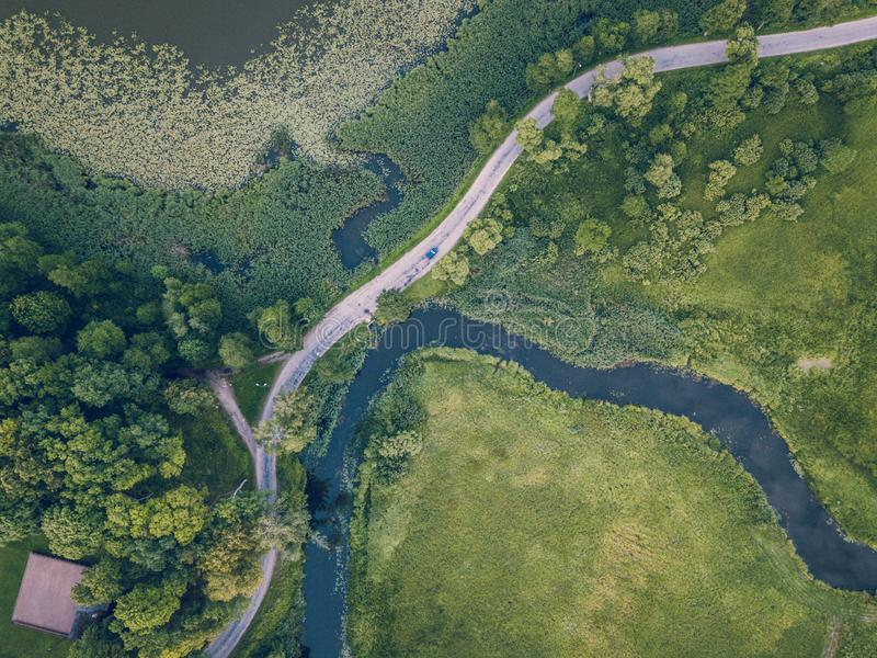 Aerial Photo of Car Driving on the Road going by the River under the Trees, Top Down View in Early Spring on Sunny Day. Concept of Peaceful Life in stock images