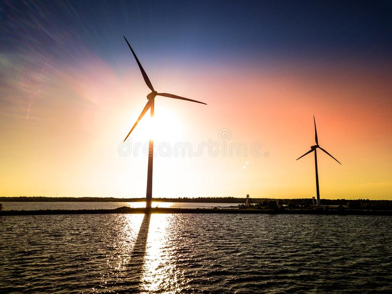Aerial photo from drone of two windmills standing at sea pier with bright colored sunset behind them, shadows are seen on wavy sea stock photos