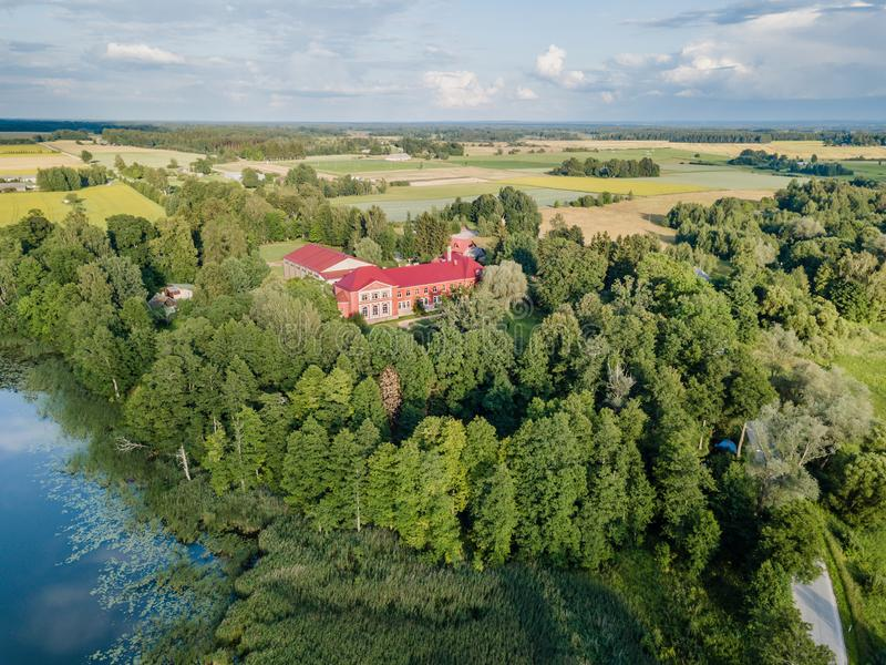 Aerial Photo of Old Castle turned into School in Countryside Between Trees with Dramatic Clouds over it in Early Spring on Sunny royalty free stock images