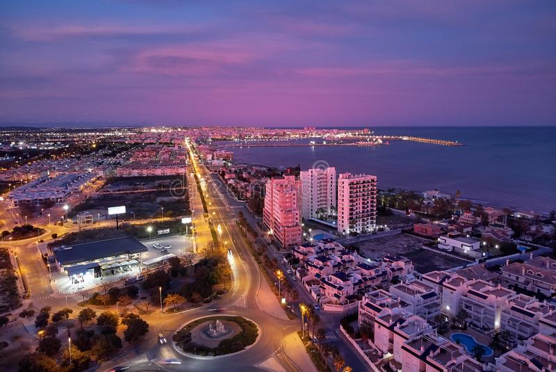 Aerial photo top view of Torrevieja spanish resort city during sunset purple violet colour cloudy sky. Picturesque sundown, Province of Alicante, Costa Blanca royalty free stock image