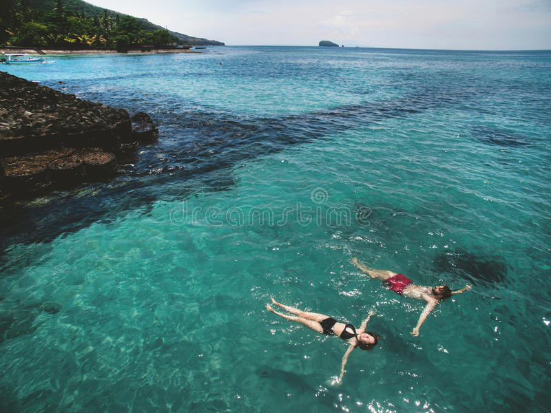 Aerial photo of young couple on holidays swimming in ocean. Aerial photo from above of beautiful young couple swimming and holding hands in the ocean at the royalty free stock photos