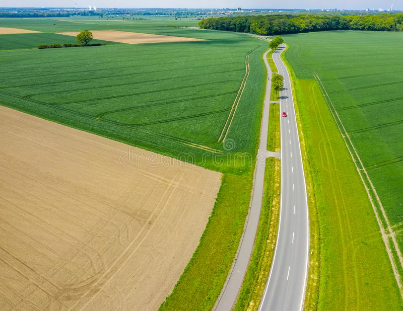 Aerial photograph with the drone camera of a small asphalted country road leading through fields and meadows, drone shot. Aerial photograph with the drone camera stock images