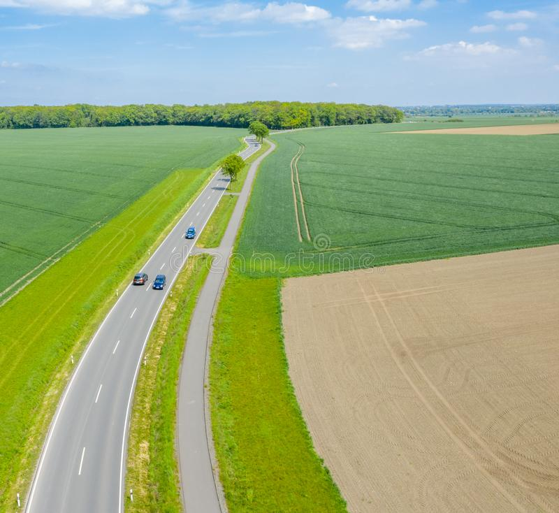 Aerial photograph with the drone camera of a small asphalted country road leading through fields and meadows, drone shot. Aerial photograph with the drone camera royalty free stock images