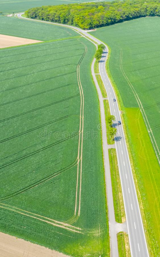 Aerial photograph with the drone camera of a small asphalted country road leading through fields and meadows, drone shot. Aerial photograph with the drone camera stock photo