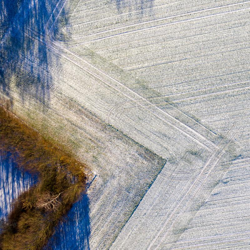Aerial photograph of a field with a thin layer of snow carefully ploughed in a geometrically rectangular shape. Drone shot stock images