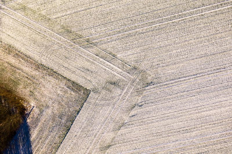 Aerial photograph of a field with a thin layer of snow carefully ploughed in a geometrically rectangular shape. Drone shot stock photos