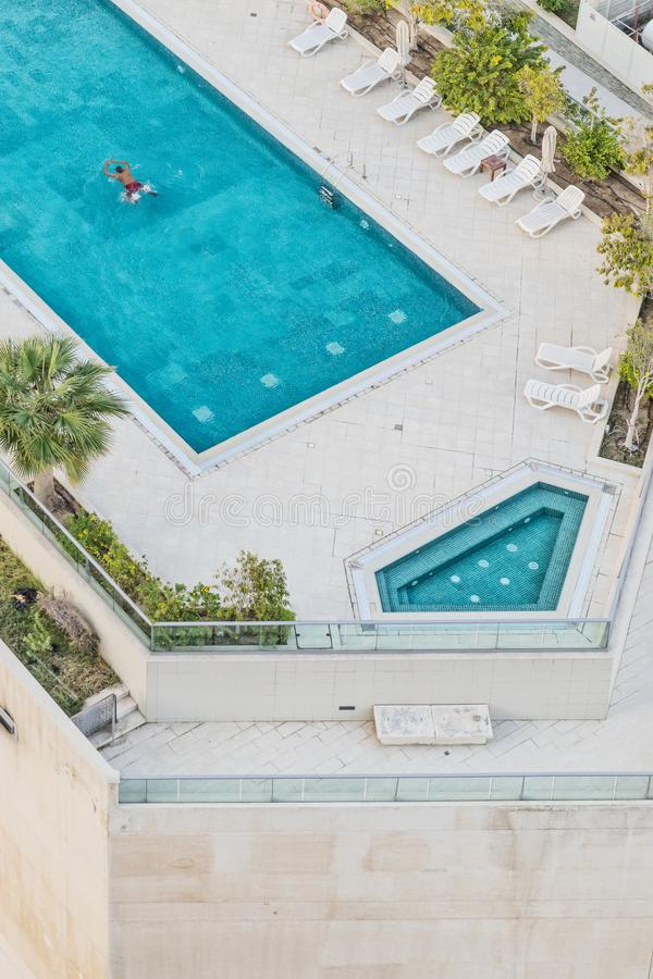 Aerial photograph of man swimming in pool with blue water. Dubai royalty free stock image