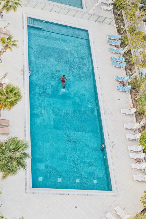 Aerial photograph of man swimming in pool with blue water. Dubai royalty free stock photos