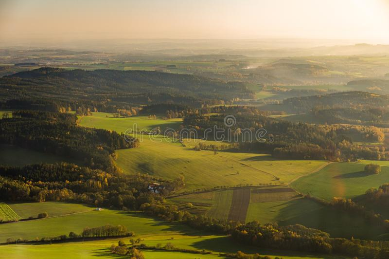 Aerial photograph of sunset over Czech Highlands with farmlands and forests stock image