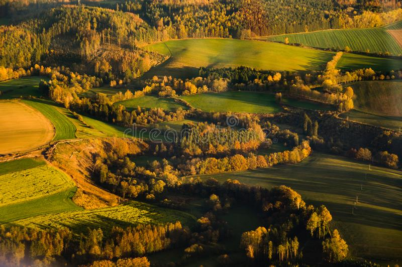 Aerial photograph of sunset over Czech Highlands with farmlands and forests royalty free stock image