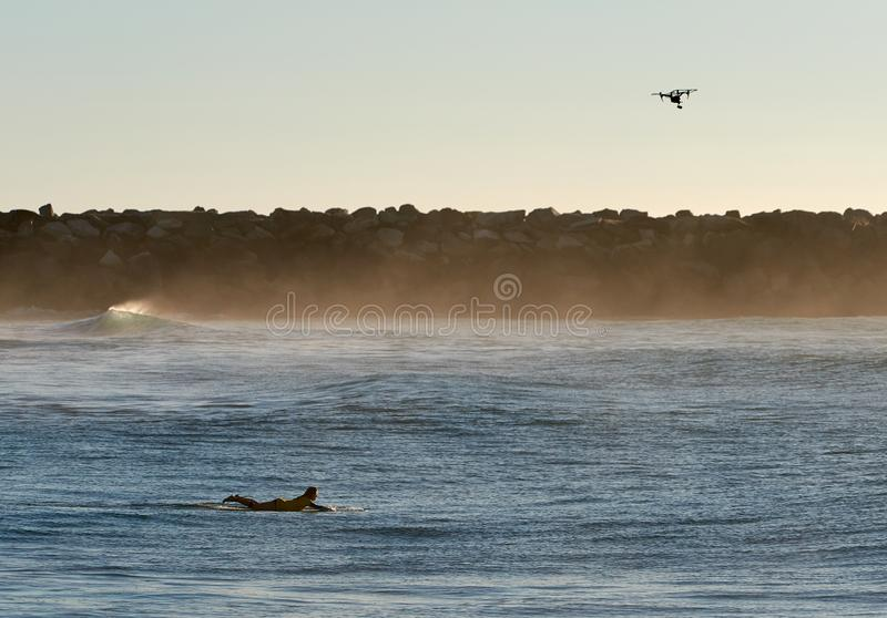 Aerial-drone tracking female surfer paddling longboard royalty free stock photos