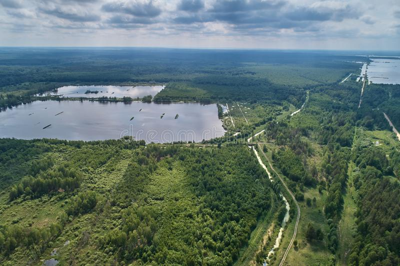 Aerial photography with a drone. Landscape with green forest, road and lake royalty free stock photos