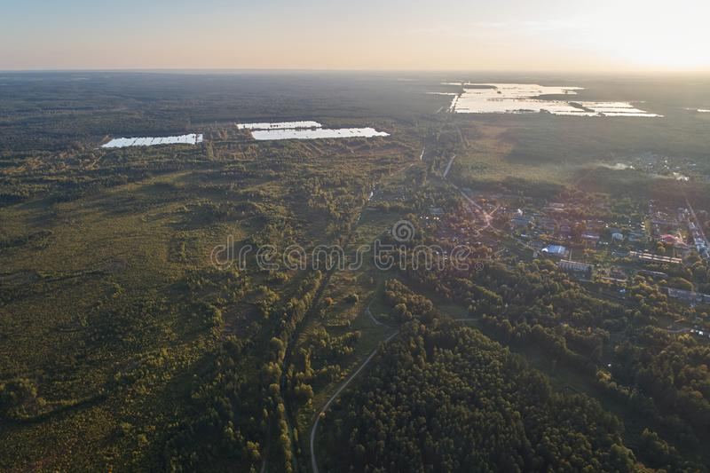 Aerial photography with a drone. Village with green forest, road and lake stock photo