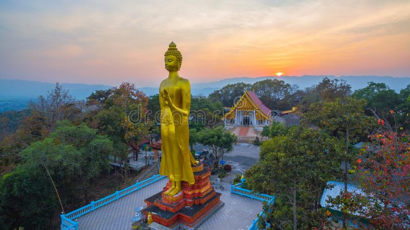 Aerial photography the golden big Buddha in Chiang Rai. Aerial photography the golden big Buddha standing statue on hilltop in sunset time at wat Phra That Jom stock photos