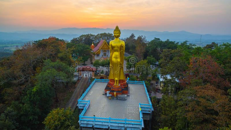 Aerial photography the golden big Buddha in Chiang Rai. Aerial photography the golden big Buddha standing statue on hilltop in sunset time at wat Phra That Jom royalty free stock image