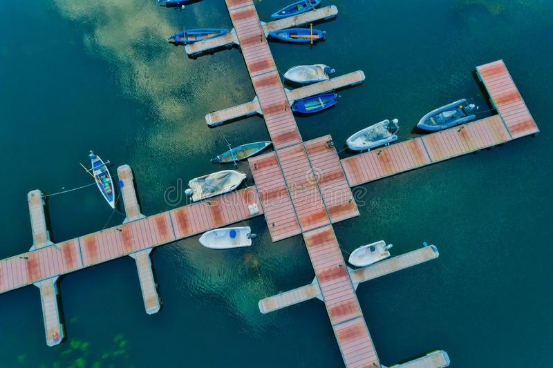 Aerial picture of floating dock with boats, motorboats and vessels floating on water in lake Small Prespes. Northern Greece stock photos