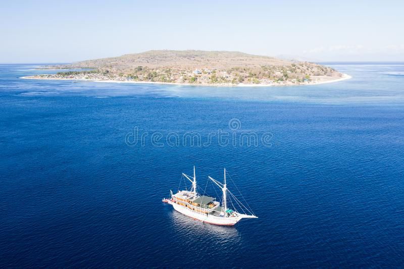 Aerial of Pinisi Schooner and Small Tropical Island in Indonesia. A Pinisi schooner rests at anchor near a remote island in Indonesia`s Banda Sea. This part of stock image