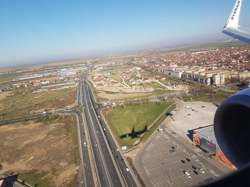 Aerial plane view of small highway roundabout, urban buildings, wing engine, Ryanair flight over City Oradae stock images