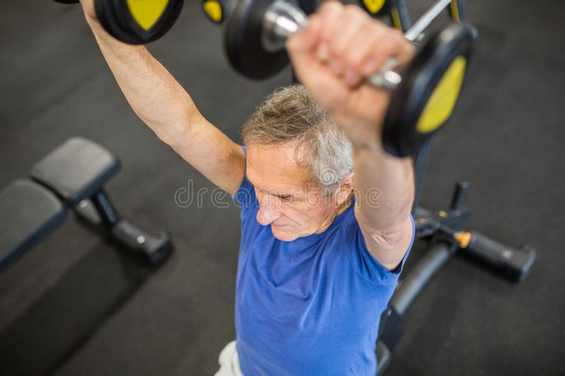 Senior man lifting weights on hammer strength machine royalty free stock photos