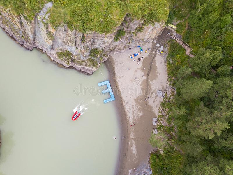 Aerial of a rubber motor boat sailing from a blue plastic pier on a green river in the mountains. Aerial view of a rubber motor boat sailing from a blue plastic royalty free stock photo