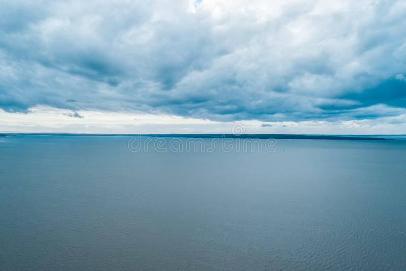 Small patch of land on the horizon - tranquil overcast scene. Aerial seascape - rain clouds over calm water and small patch of land on the horizon - tranquil stock photography