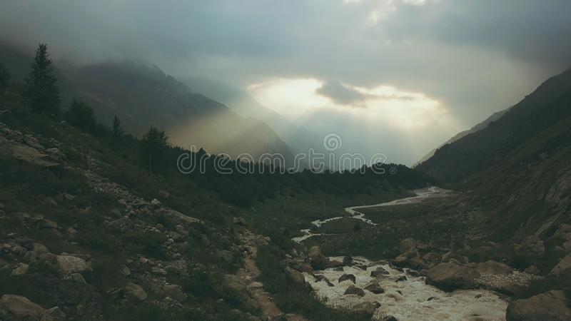 Aerial shooting from flying drone river in mountain. Tourist on mountain road stock image