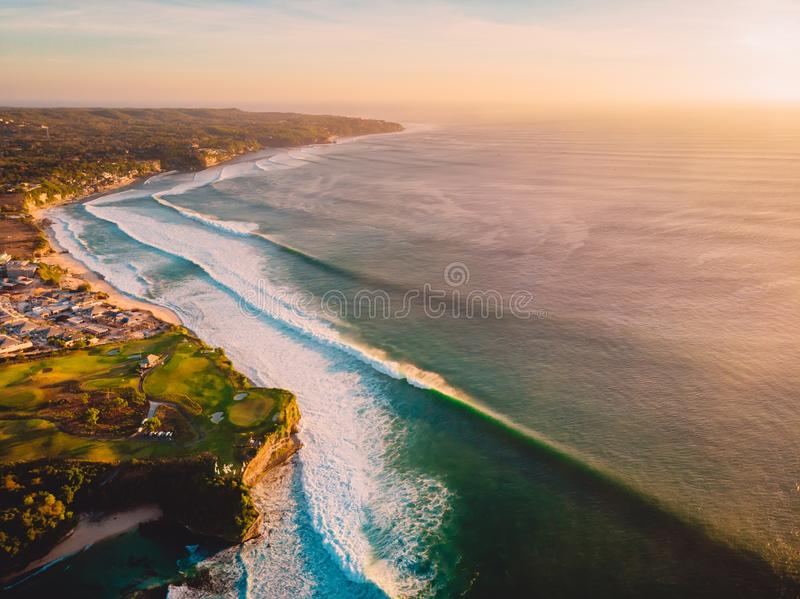Aerial shooting of waves in ocean and shore at sunset royalty free stock photography