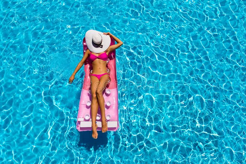 Attractive woman is relaxing on a floating mattress in a pool royalty free stock image