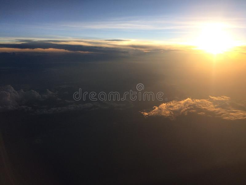 Aerial shot of a beautiful sky and clouds with the sun shining in the background. An aerial shot of a beautiful sky and clouds with the sun shining in the royalty free stock photos