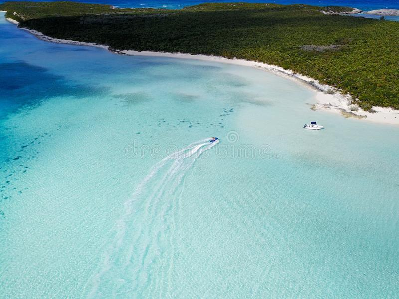 Aerial shot of boats in the ocean near a green island in Exuma. An aerial shot of boats in the ocean near a green island in Exuma stock image