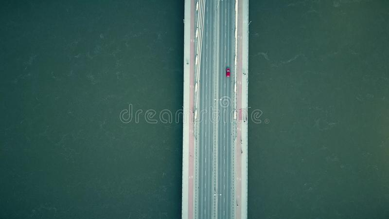 Aerial shot of the cable bridge with pedestrians, bicycles and red car crossing the river, top view stock photo