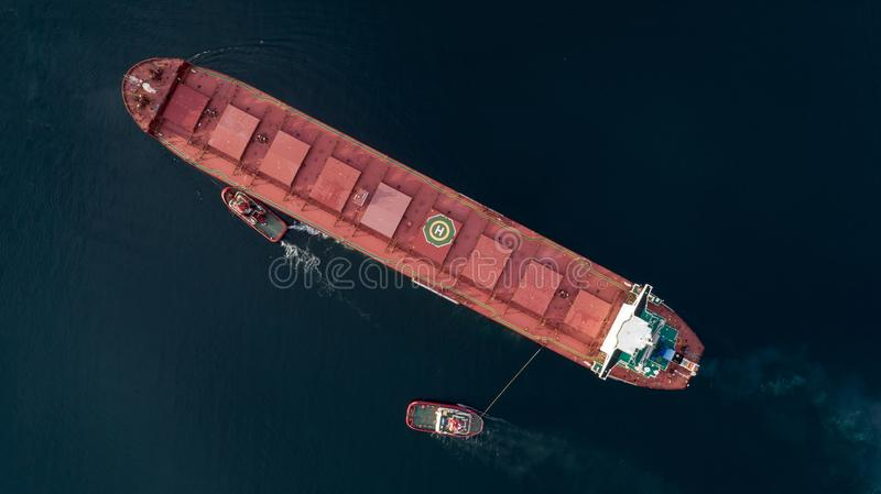 Aerial shot of a cargo ship approaching port with help of towing ship royalty free stock image
