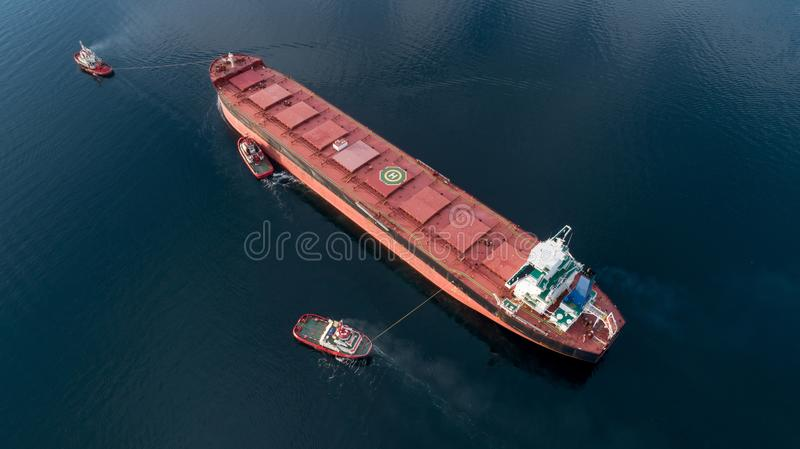 Aerial shot of a cargo ship approaching port with help of towing ship royalty free stock images