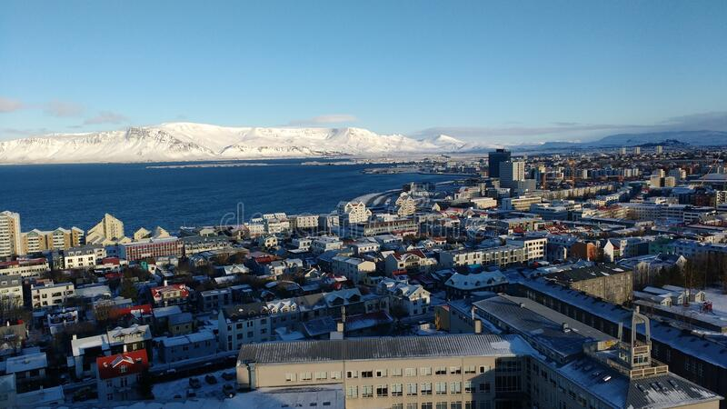 Aerial shot of the coastal city of Reykjavik, Iceland with a snow covered mountain. An aerial shot of the coastal city of Reykjavik, Iceland with a snow covered stock photos
