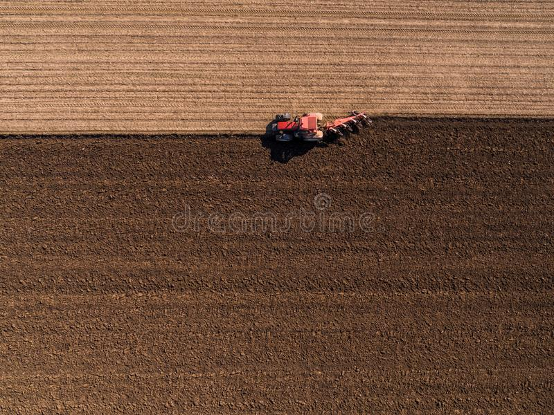 Aerial shot of a farmer plowing stubble field. Agricultural activity royalty free stock image