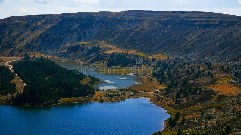 Aerial shot of green mountains next to a river in Neila lagoon, Spain. An aerial shot of green mountains next to a river in Neila lagoon, Spain stock photography