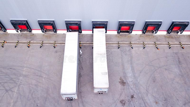 Aerial Shot of Industrial Warehouse Loading Dock where Many Truck with Semi Trailers Load Merchandise. Aerial. Drone royalty free stock photos