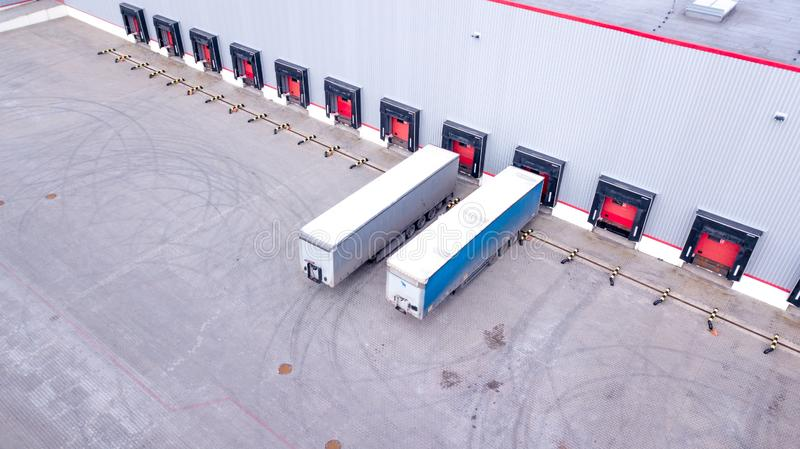 Aerial Shot of Industrial Warehouse Loading Dock where Many Truck with Semi Trailers Load Merchandise. Aerial. Drone royalty free stock photo