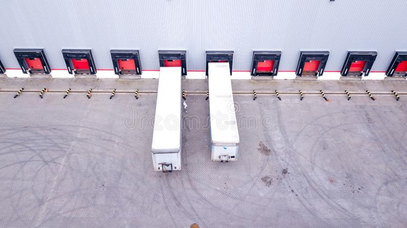 Aerial Shot of Industrial Warehouse Loading Dock where Many Truck with Semi Trailers Load Merchandise. Aerial. Drone stock photography