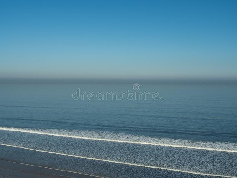 An aerial shot of a lone surfer paddling out to sea on a hazy summer day. The beautiful blue ocean appears still and calm apart from the breaking waves royalty free stock photos