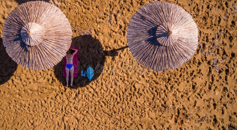 Aerial shot of a lone woman relaxing under an umbrella on the beach. Amazing Greece royalty free stock photos