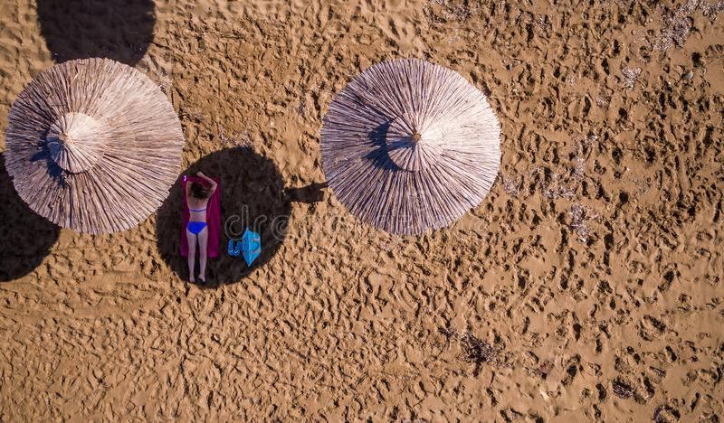 Aerial shot of a lone woman relaxing under an umbrella on the beach. Amazing Greece stock photo